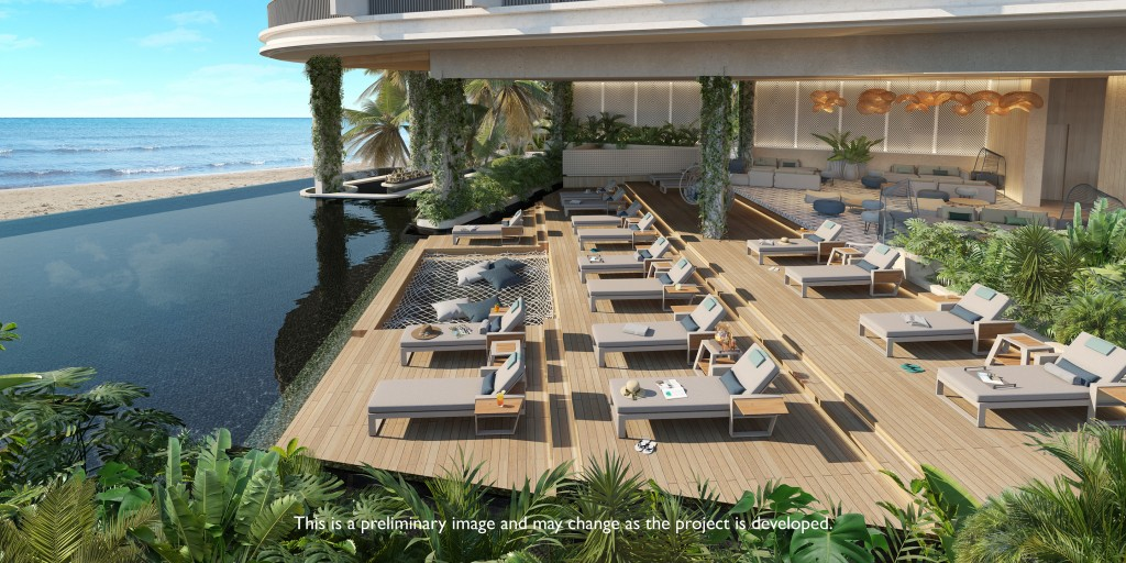An oceanfront rooftop pool deck with three rows of lounge chairs.