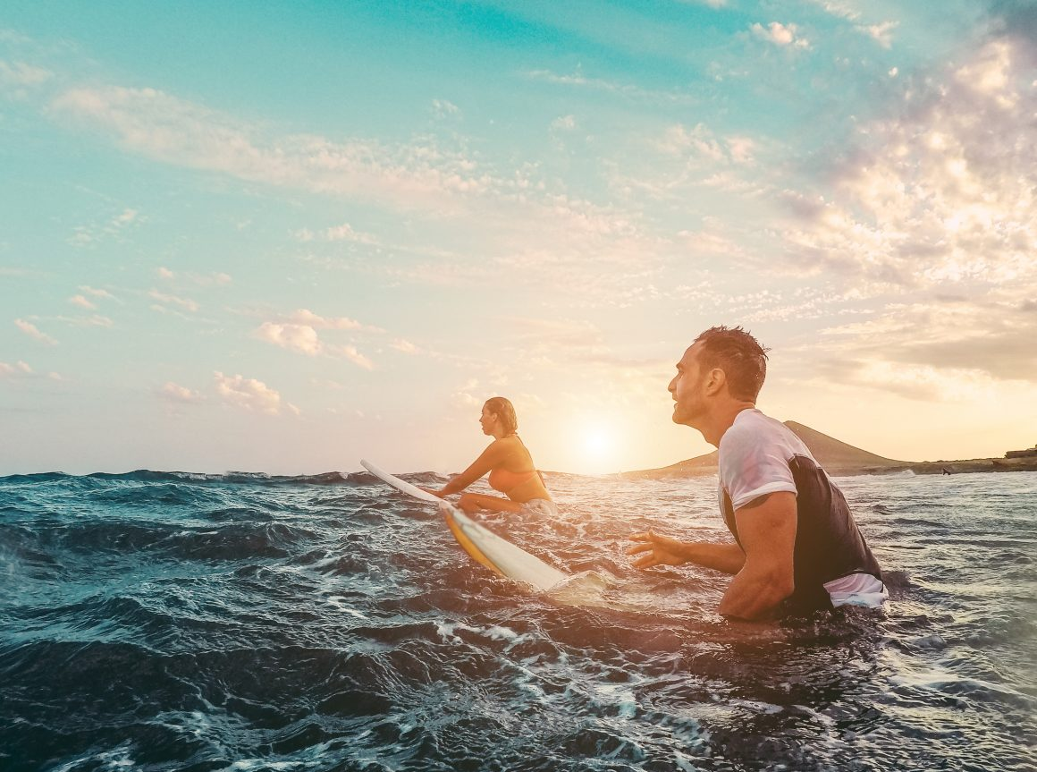 A male and female surfer riding out on their surfboards at sunrise.