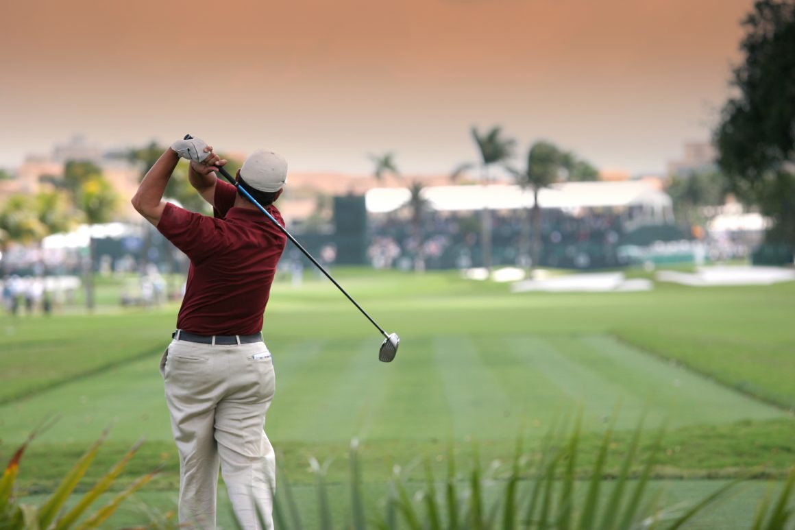 A golfer swings his club on a tropical course at sunset.