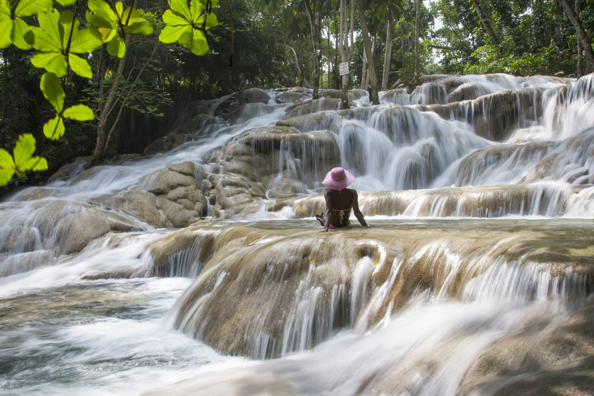 A young woman watching a waterfall.