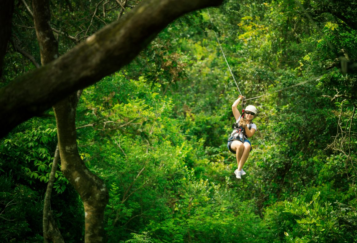 A woman in her 40s riding a zipline between trees.