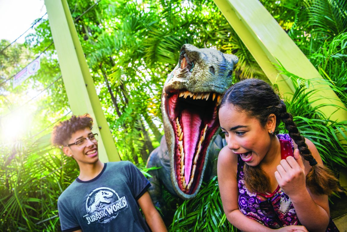 """An animatronic velociraptor with its jaws wide open pops up between a laughing boy in a """"Jurassic World"""" t-shirt and a screaming girl at Universal's Islands of Adventure theme park."""