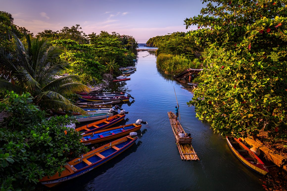 A man steers a bamboo raft with two seated passengers past a row of boats on a river at sunset.