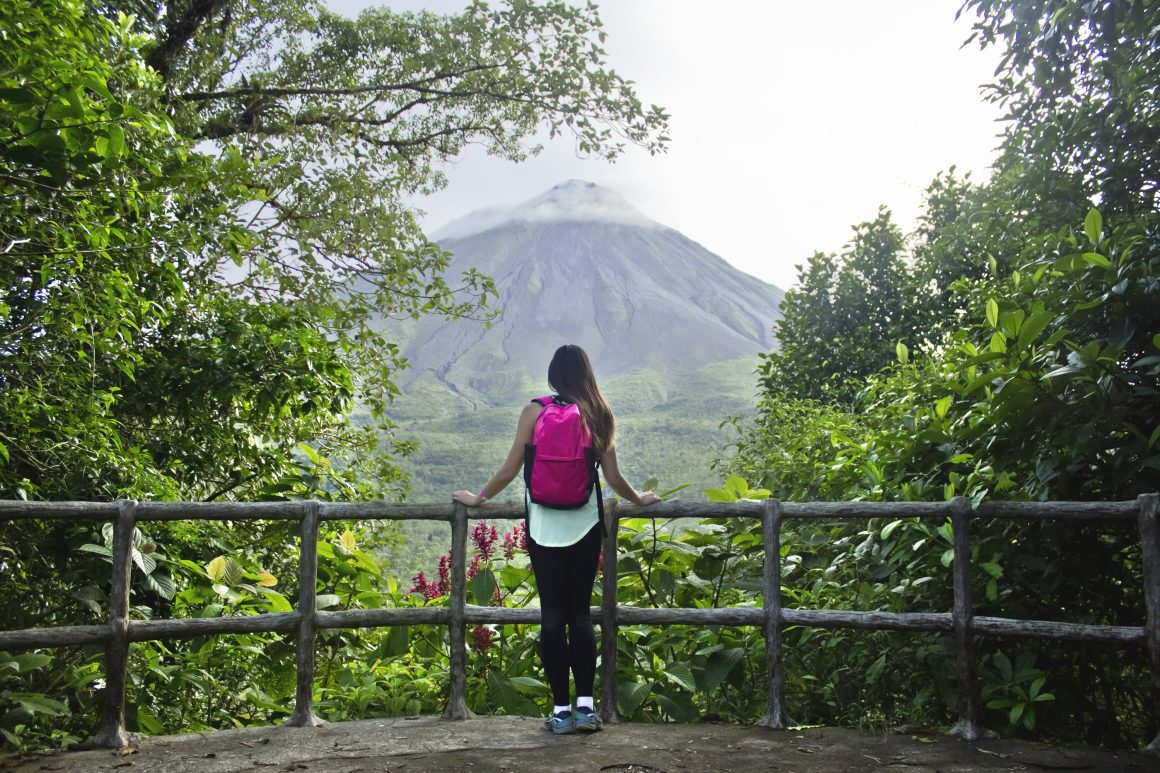 A woman gazes out at Arenal Volcano from an observation point.