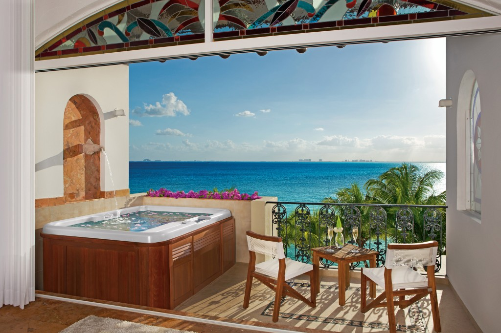A Jacuzzi, table, and chairs on a terrace overlooking the ocean.