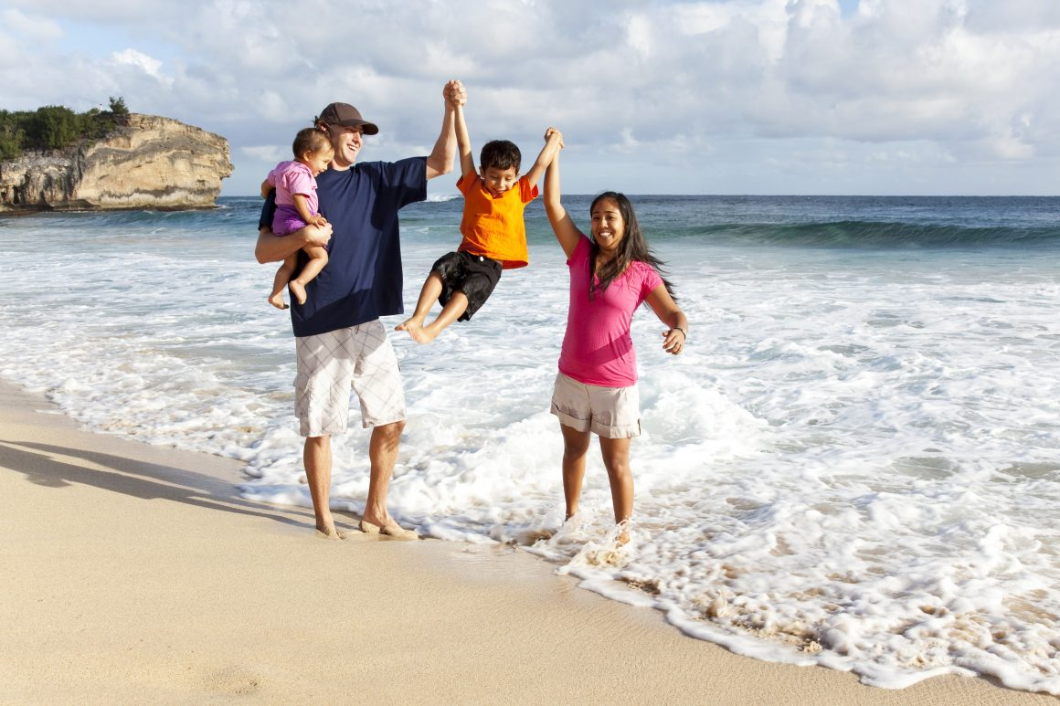 A family walks along the shoreline, lifting their son into the air above the waves.