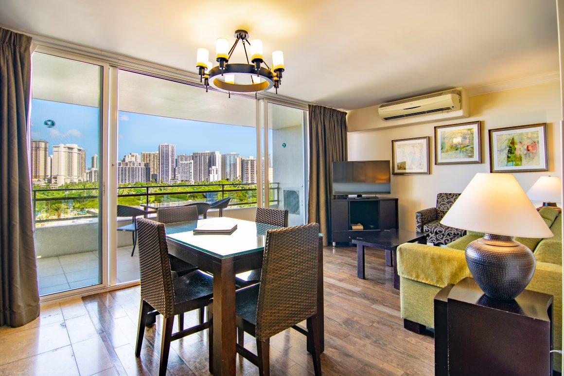 An open dining and sitting area in a Two Bed Partial Ocean View unit with the Honolulu skyline visible through floor-to-ceiling glass doors.