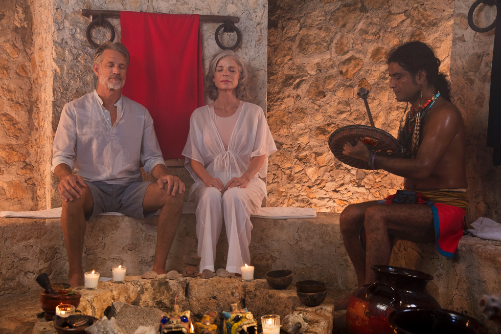 Older couple sitting with a healer in a Mayan sweat lodge