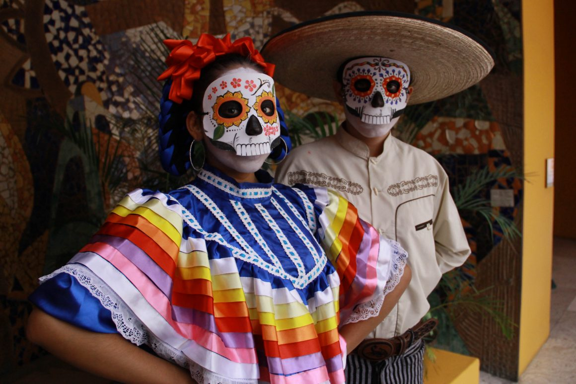 A man and woman wear traditional shirts and skull masks for the Day of the Dead
