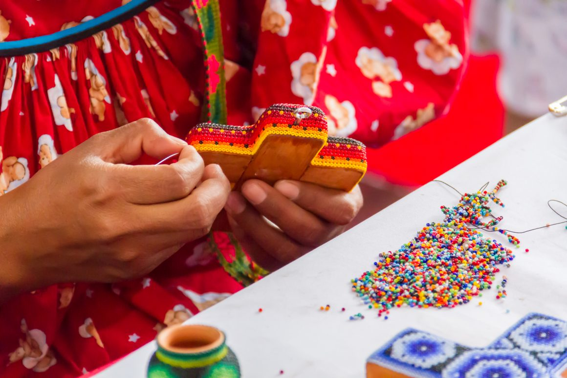 Woman creating traditional beaded craft