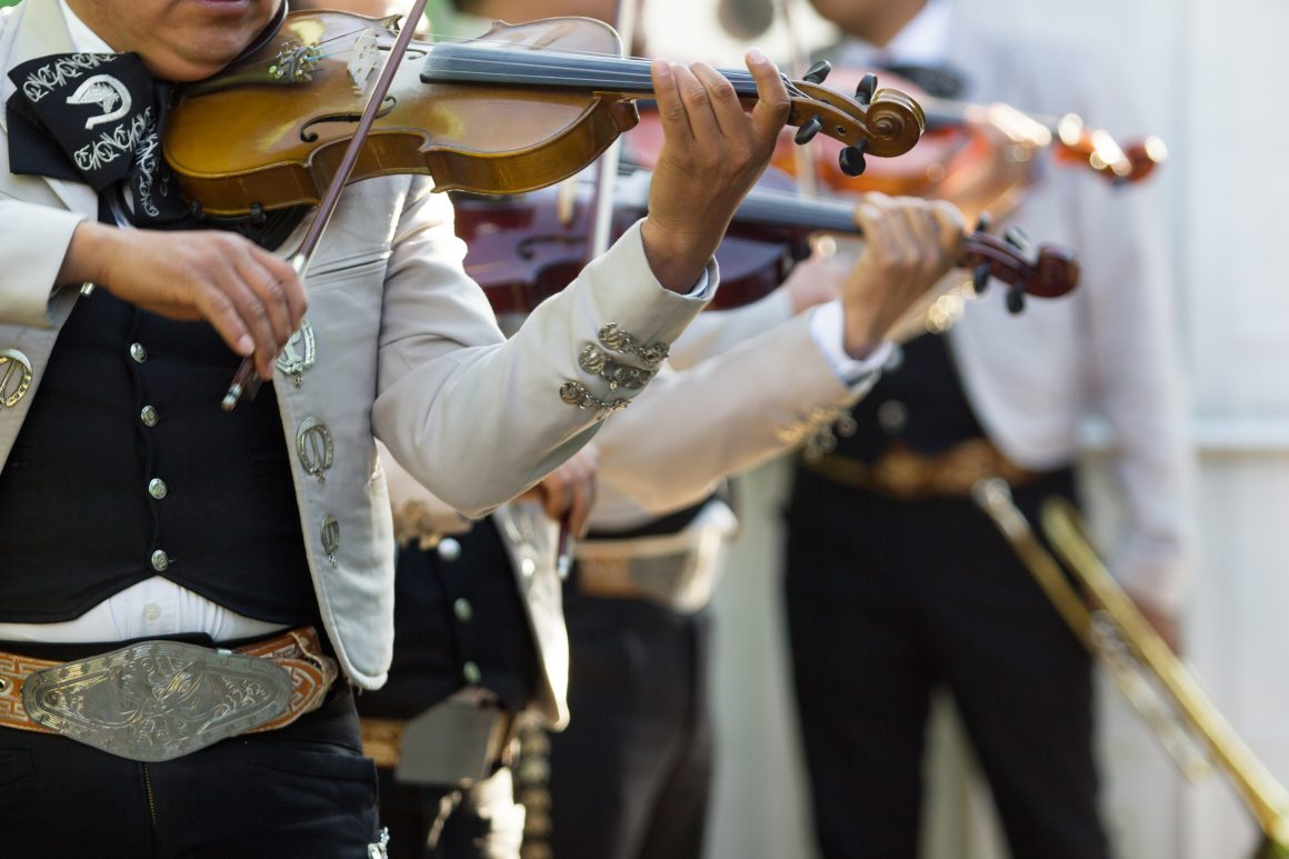 Two members of a mariachi band playing the violin