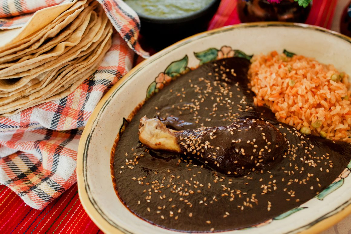 A chicken and rice dish topped with mole poblano