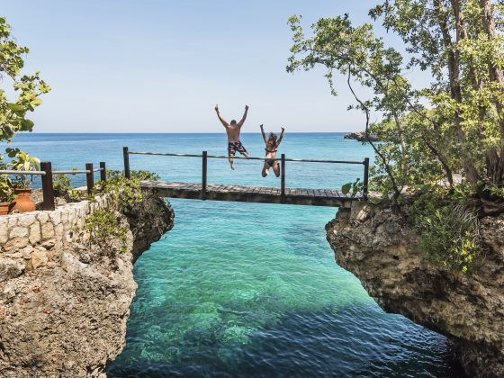 A man and a woman jumping off of a low wooden bridge into the ocean below.