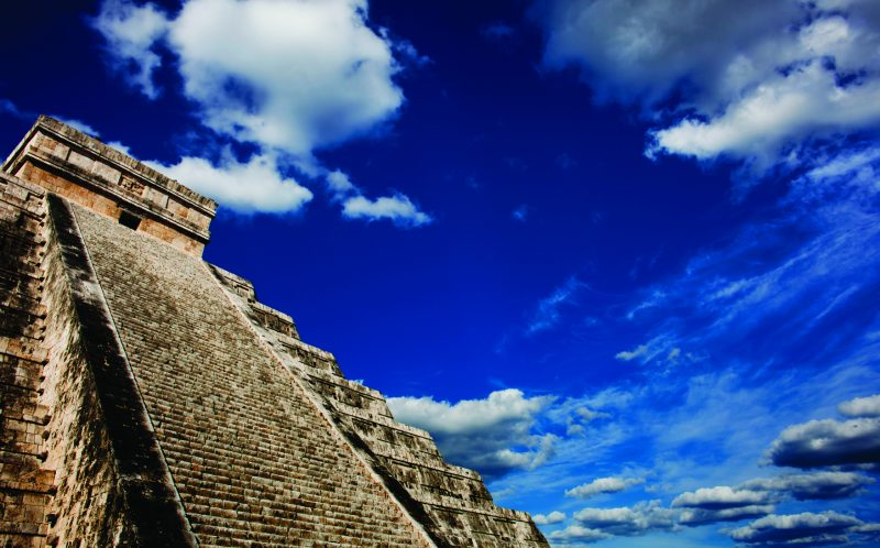 The ancient El Castillo pyramid at Chichen Itza against the backdrop of a bright blue sky with clouds.