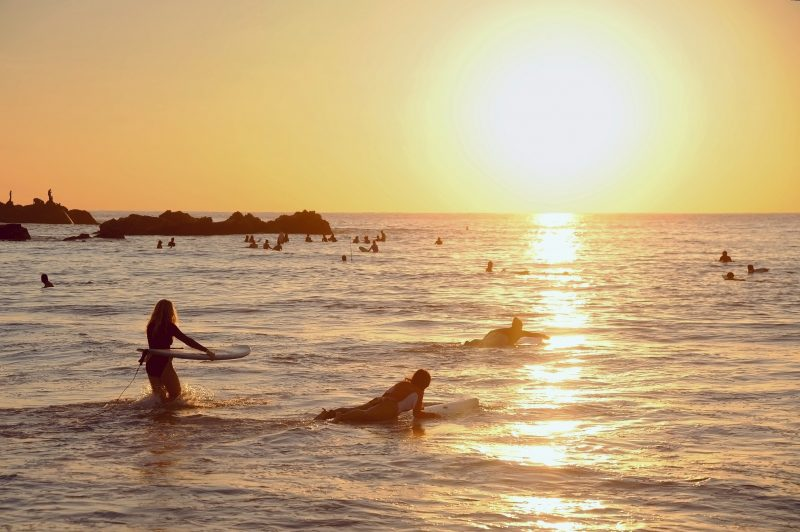 Surfers ride out at sunset