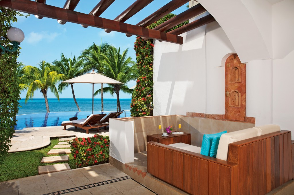 The seating area of a terrace with a pathway leading to a private infinity pool beside the ocean.