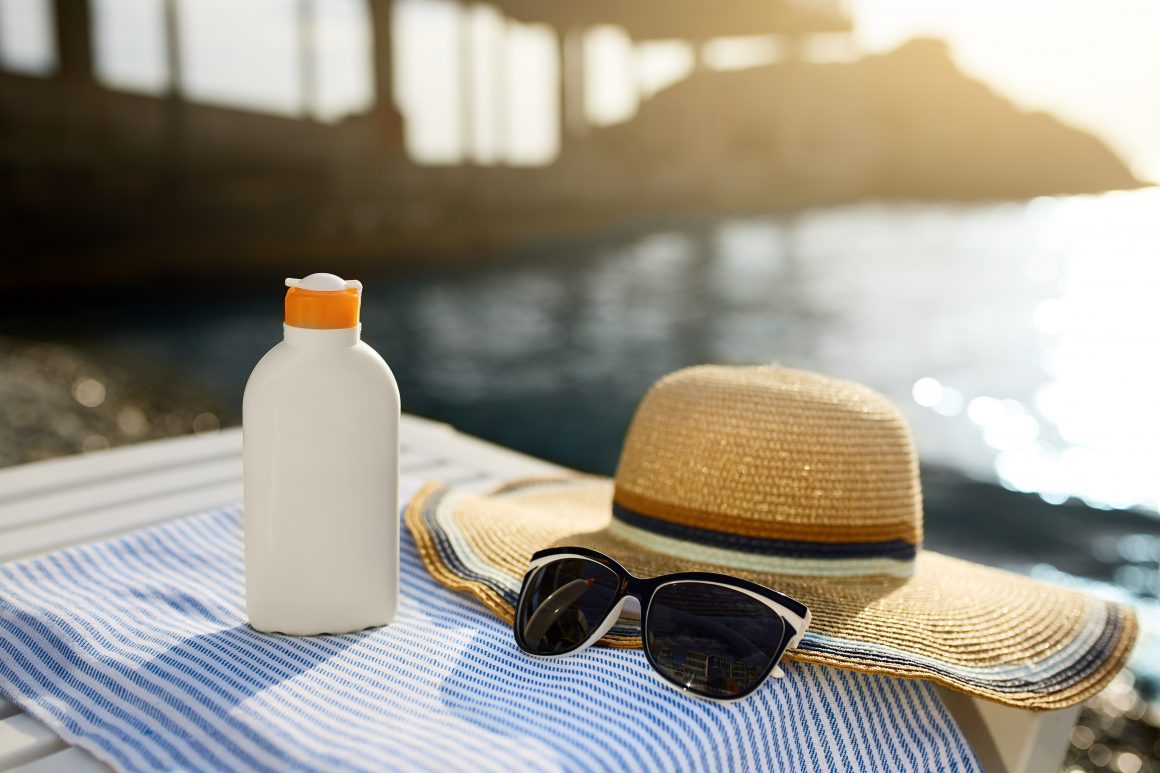 Sunglasses, sunscreen bottle, and sunhat on a blue towel with an ocean pier in the background.
