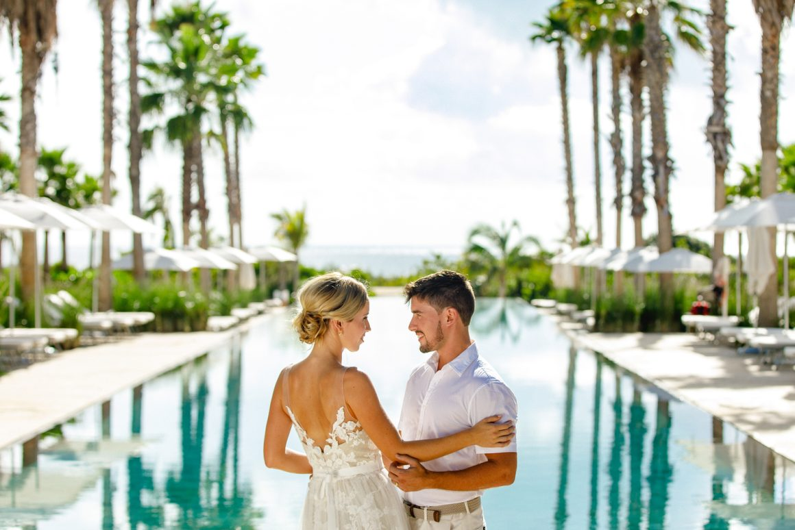 Bride and groom in front of an infinity pool.